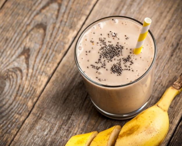 Bicchiere da frullato al cioccolato e banana sul tavolo di legno