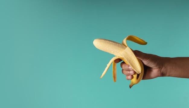 Immagine di concetto di banana. mano che tiene una buccia di banana contro lo sfondo blu, sembra una pistola