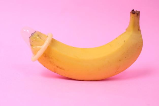 Banana e contraccezione isolati su sfondo rosa