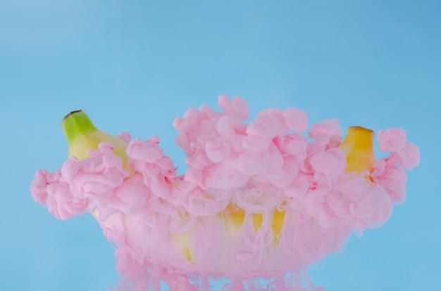 Un frutto di banana con parziale attenzione alla dissoluzione del colore rosa del poster in acqua su sfondo blu.