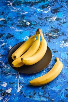 La banana fruttifica in banda nera su fondo strutturato blu, spazio della copia di vista di angolo