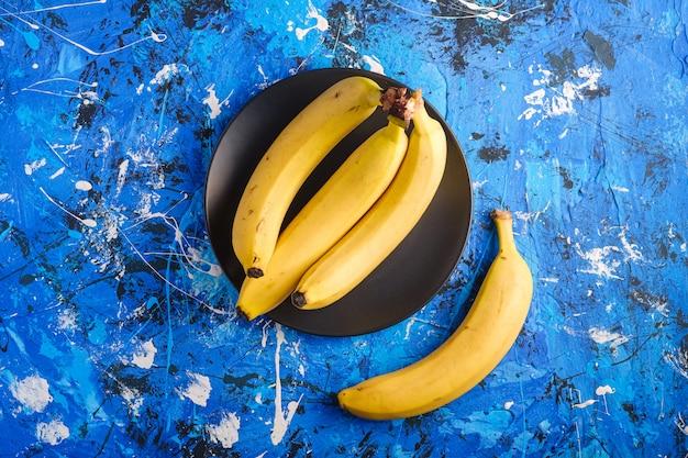 La banana fruttifica in banda nera su fondo strutturato blu, spazio della copia di vista superiore