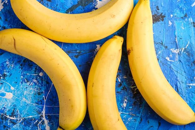La banana fruttifica su fondo strutturato blu, vista superiore
