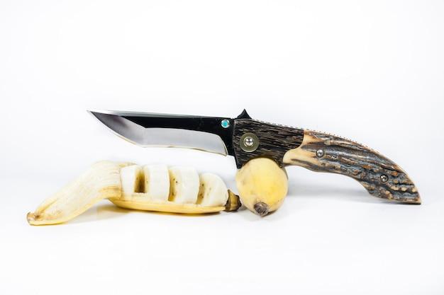 Banana e coltello su sfondo bianco.