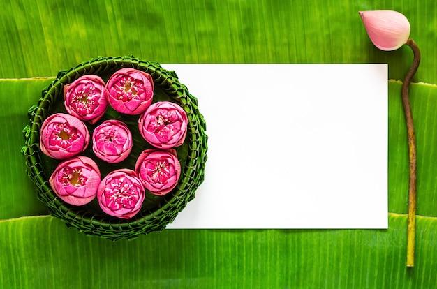 Foglia di banana krathong decora con fiori di loto rosa per la thailandia luna piena o festival loy krathong con spazio per il testo.