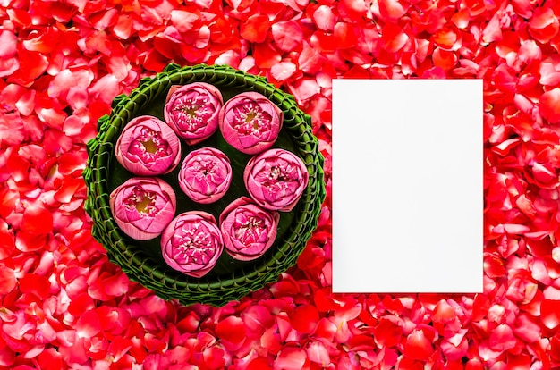 Foglia di banana krathong con fiori di loto per la thailandia luna piena o festival di loy krathong con spazio per il testo su sfondo di petali di rosa rossa.