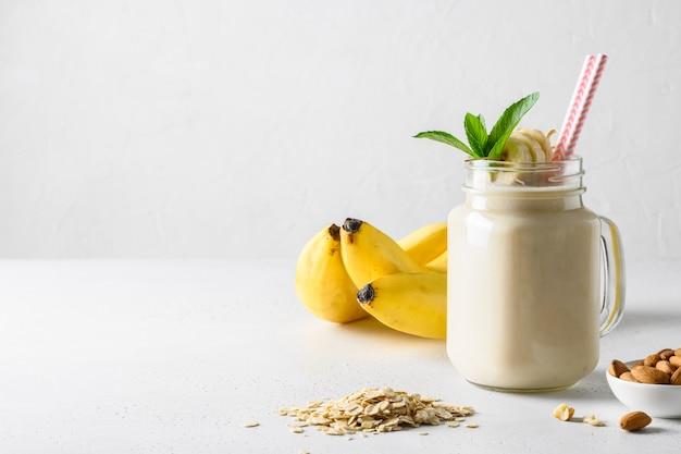 Frappè della banana in barattolo di muratore sul bordo bianco. formato verticale