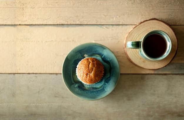 Muffin alla banana e caffè caldo sul tavolo di legno. stile rustico.