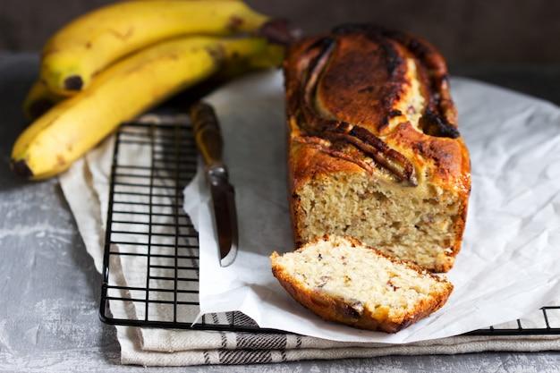 Muffin alla banana con zenzero candito e uvetta e banane su uno sfondo grigio.