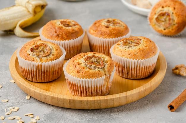 Muffin alla banana con farina d'avena, noci e cannella su un vassoio di legno su sfondo grigio