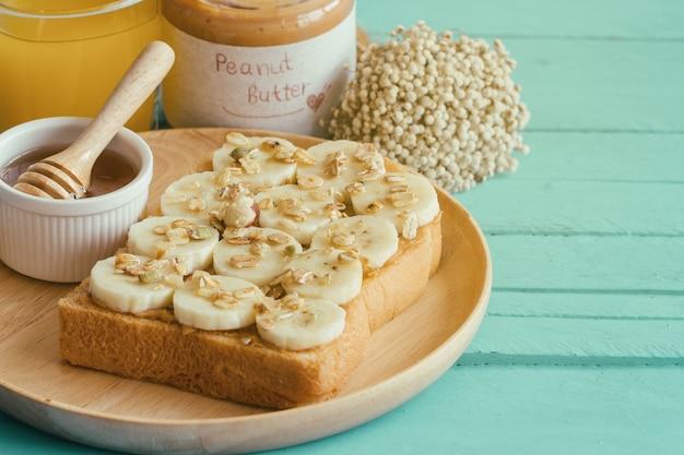 Sandwich aperto di fronte al pane tostato del burro di arachidi della banana