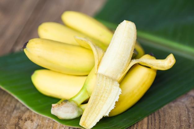 Buccia di banana pronta da mangiare e frutta banana matura su sfondo foglia di banana