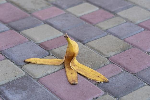 La buccia di banana è stata lasciata sul marciapiede. il pericolo può scivolare. se qualcuno ci cammina sopra. fai attenzione allo scivoloso. vicino, all'aperto