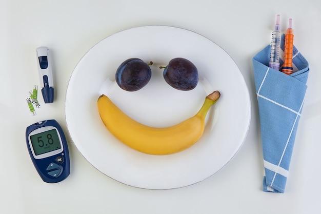 Banana e prugna sotto forma di emoticon sorridente
