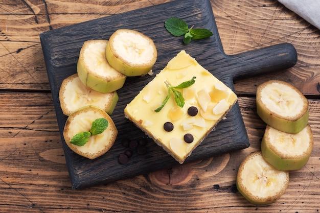 Pan di spagna alla banana con noci e gocce di cioccolato. delizioso dessert dolce per il tè, sullo sfondo di legno. vista dall'alto, copia dello spazio.