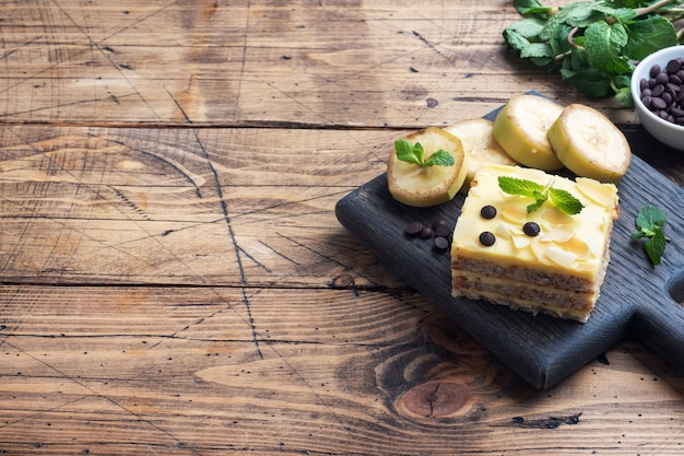 Pan di spagna alla banana con noci e gocce di cioccolato. delizioso dessert dolce per il tè, fondo in legno. vista dall'alto, copia spazio.