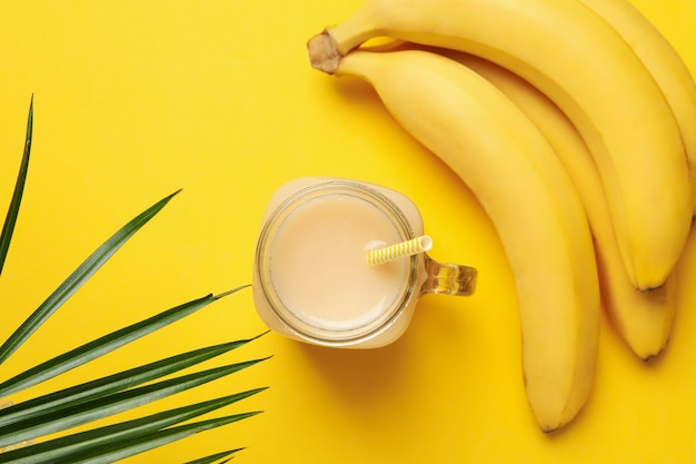 Banane e succo su sfondo giallo. frutta fresca