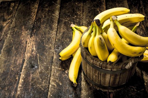 Banane in un secchio di legno. su uno sfondo di legno.