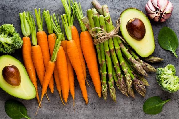 Banches di asparagi verdi freschi e verdure sulla tavola di legno, vista dall'alto