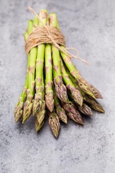 Banches di asparagi verdi freschi e verdure sulla tavola di legno