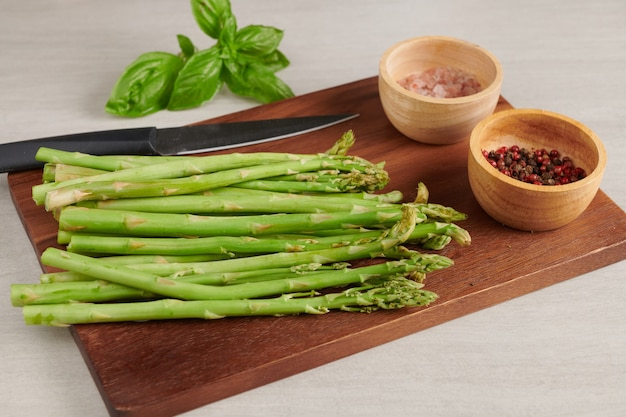 Banches di asparagi verdi freschi su una superficie di legno