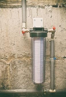 Una fascia nuova per il filtro dell'acqua con tubi di plastica nel seminterrato
