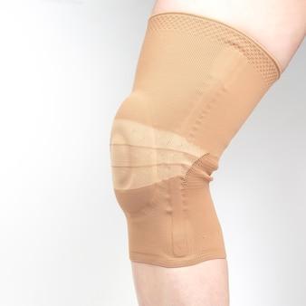 Benda per il fissaggio del ginocchio ferito della gamba umana su uno sfondo bianco.