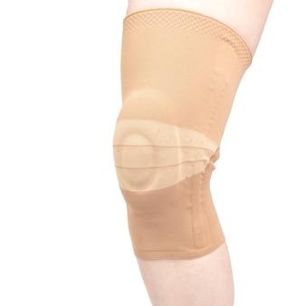 Benda per il fissaggio del ginocchio ferito della gamba umana su un bianco