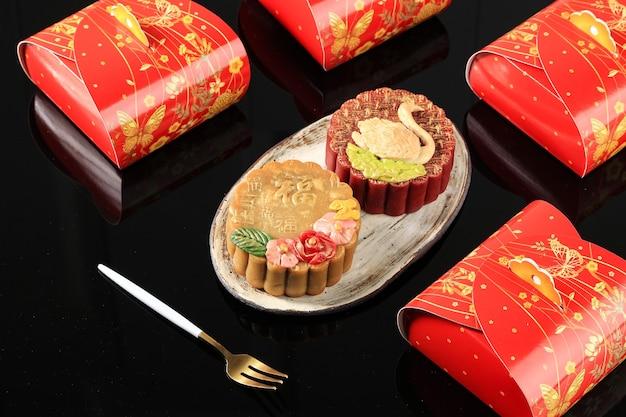 Bandung, indonesia, 02092021: torta di luna premium fatta in casa (torta di luna) con polvere d'oro isolata su sfondo nero. concetto per mid autumn festival con copia spazio per text