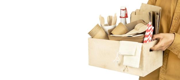 Baner con un corriere che tiene una scatola con piatti ecologici per fast food con piatti sctaans posate