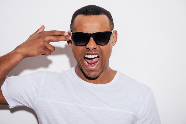 Scoppio! furioso giovane africano in occhiali da sole che gesticola con la pistola a dito vicino alla testa e tiene la bocca aperta