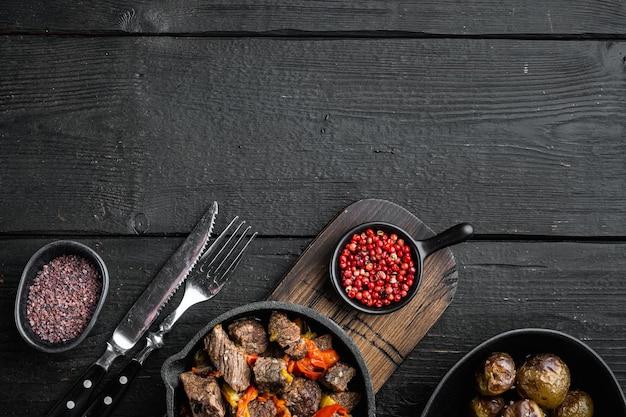 Spezzatino di manzo bangin servito, in padella in ghisa, sul tavolo di legno nero, vista dall'alto laici piatta