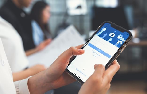 Bangkok, tailandia - 6 aprile 2020: la mano della donna sta premendo lo schermo di facebook su apple iphone, i social media stanno usando per la condivisione delle informazioni e il networking.