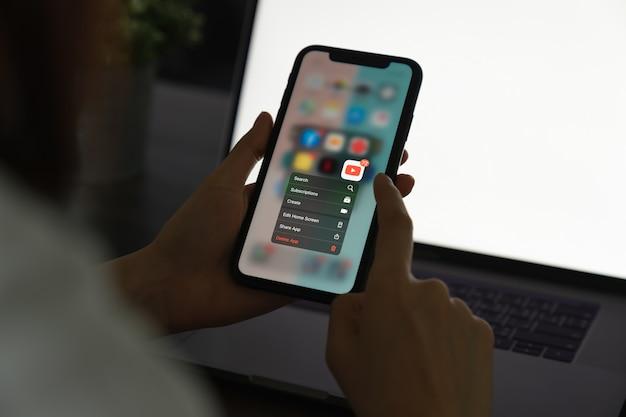 Bangkok, thailandia - 15 aprile 2020: la mano tiene il telefono ed elimina l'applicazione dello schermo di youtube sull'iphone 11 di apple.