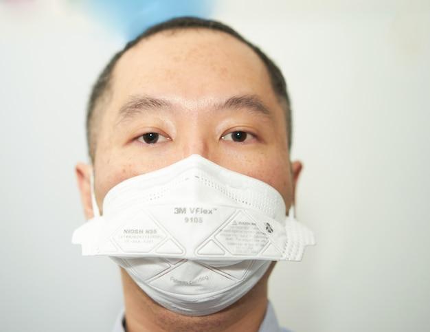 Bangkok, thailandia,-asia uomo indossa la maschera del virus corona di protezione n95 isolata su whtie in pandemia covid 19 guarda la fotocamera