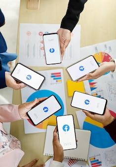 Bangkok/thailandia - 6 agosto 2021: le persone tengono in mano smartphone di diverse marche e vari sistemi operativi con i loghi di facebook, le applicazioni di social network più popolari.