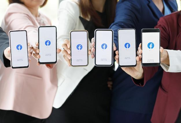 Bangkok/thailandia - 6 agosto 2021: le persone tengono in mano smartphone di marche diverse e vari sistemi operativi con i loghi di facebook, le applicazioni di social network più popolari.