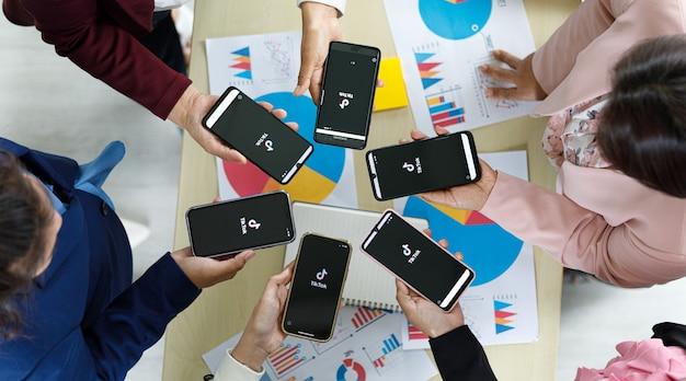 Bangkok/thailandia - 06 agosto 2021: le persone tengono in mano smartphone di diverse marche e vari sistemi operativi con loghi tiktok, uno dei social network video più popolari.
