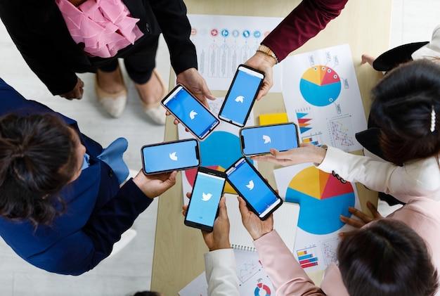 Bangkok/thailandia - 6 agosto 2021: le persone tengono in mano smartphone di marche diverse e vari sistemi operativi con loghi delle applicazioni social di twitter.
