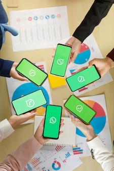 Bangkok/thailandia - 06 agosto 2021: le persone tengono in mano smartphone di diverse marche e vari sistemi operativi con loghi di whatapp, popolari applicazioni messege di social network.