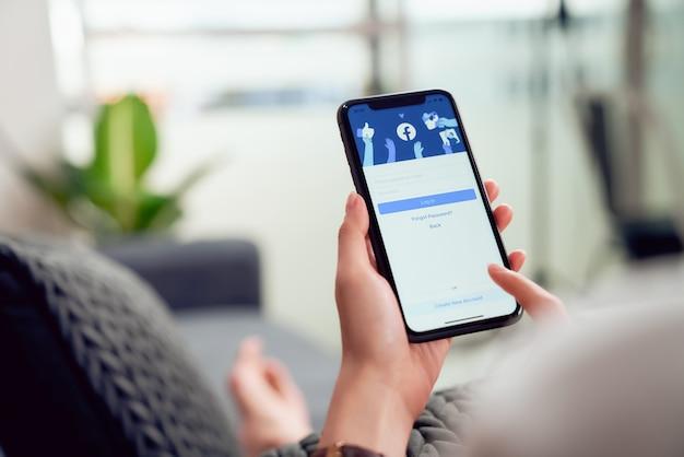 Bangkok, tailandia - 28 gennaio 2020: la mano della donna sta premendo lo schermo di facebook su apple iphone, i social media stanno usando per la condivisione delle informazioni e il networking.
