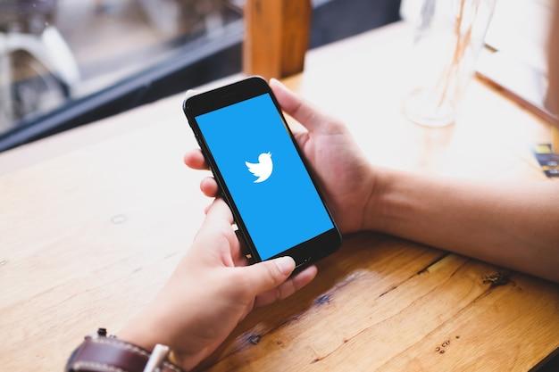 Bangkok. tailandia. 20 giugno 2020: primo piano dell'uomo che tiene in mano lo smartphone e inizia a utilizzare l'applicazione twitter.