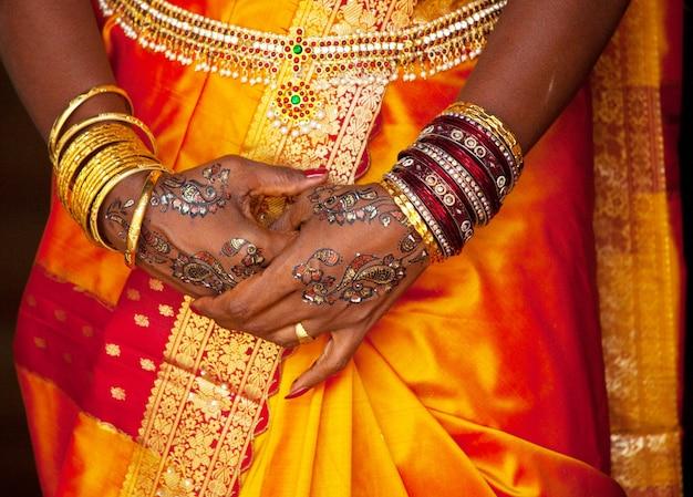 Braccialetti, anelli e motivo nuziale sulle mani