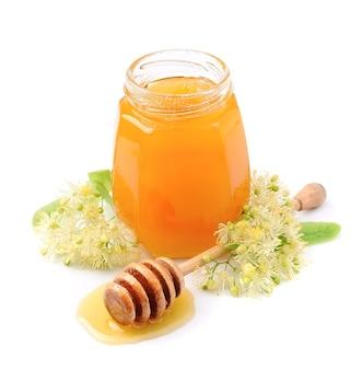 Banca di miele con fiori di tiglio da vicino.