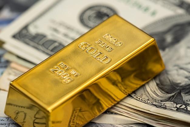 Barra d'oro da investimento bancario e banconota da soldi americani