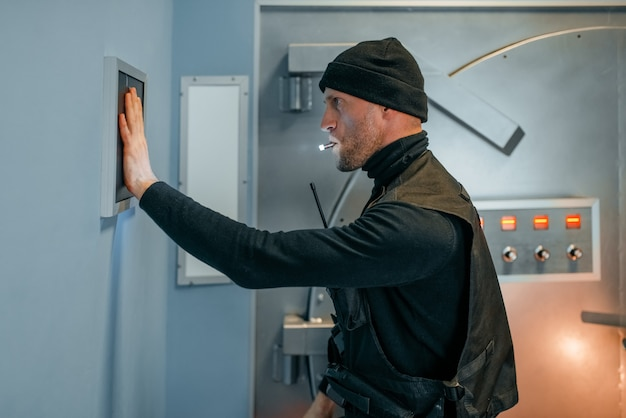 Rapina in banca, rapinatore in uniforme nera che cerca di aprire la porta del caveau. professione criminale, concetto di furto
