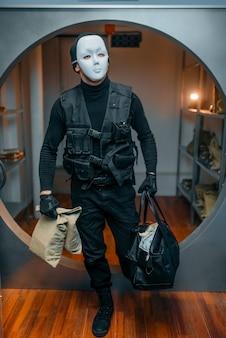 Rapina in banca, rapinatore in uniforme nera e maschera