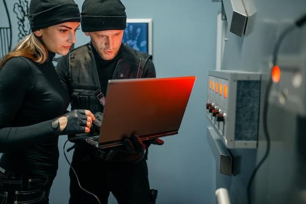 Rapina in banca, due rapinatori con laptop che cercano di aprire la porta del caveau. professione criminale, concetto di furto