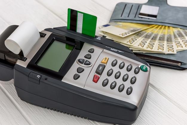 Terminale bancario con euro in portafoglio e carta di credito
