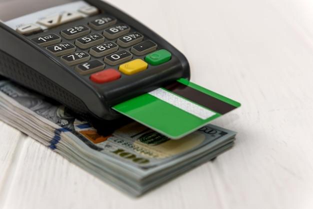 Terminale bancario con carta di credito verde e superficie in dollari
